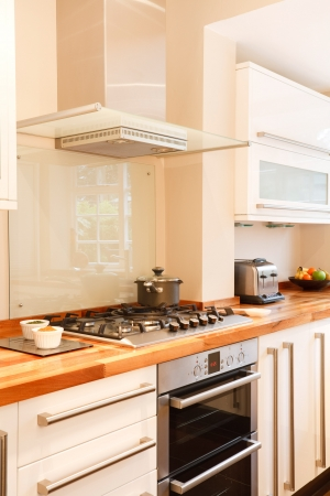 cor: Modern white kitchen with stainless steel cooker, gas hob and chimney extractor