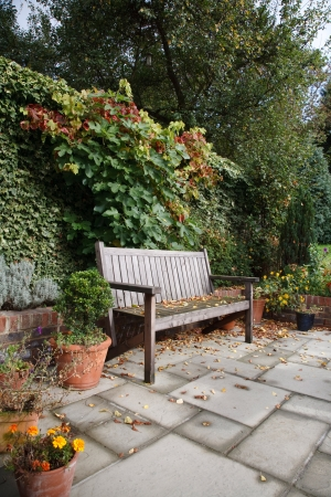 An informal English garden in autumn with traditional wooden bench, flagstones and terracotta plant pots photo