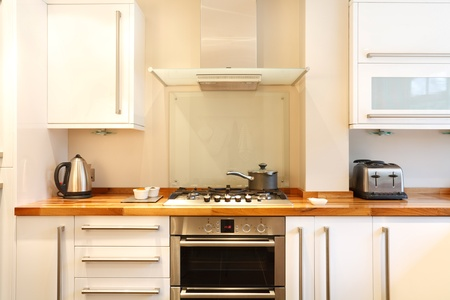 worktops: Modern kitchen with a gas hob, chimney hood, wooden worktops and stainless steel appliances Stock Photo