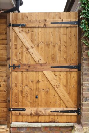 Tongue and groove exterior wooden garden door with cast iron hinges photo