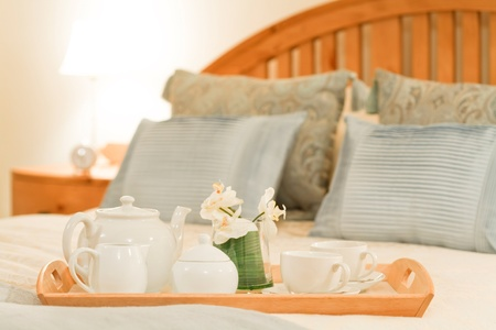 lodging: Breakfast tray on a bed in a traditional style bedroom