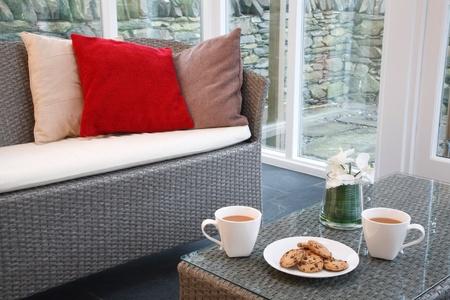 Conservatorium interieur met rotan stoelen en een koffietafel Stockfoto