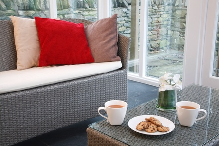cosy: Conservatory interior design with rattan chairs and coffee table