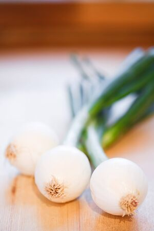 spring onions: Raw spring onions on a wooden kitchen worktop with copyspace