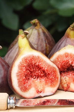 purple fig: Freshly cut figs on a table or chopping board, with the leaves of a fig tree in the background Stock Photo