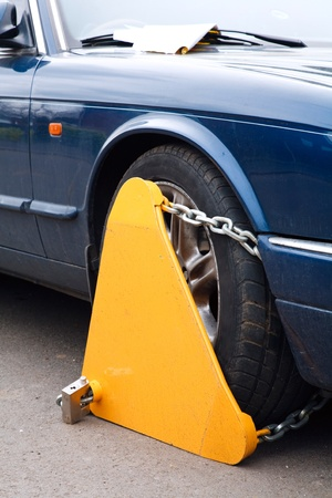 offenses: Closeup of a yellow wheel clamp attached to the wheel of a car
