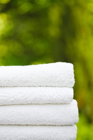 heap up: Stack of fresh white towels in a garden setting with copyspace, ideal for depicting a day spa or wellness