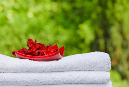 Pile of fresh white towels and rose petals with greenery in the background and space for text, ideal for depicting leisure or a spa resort photo