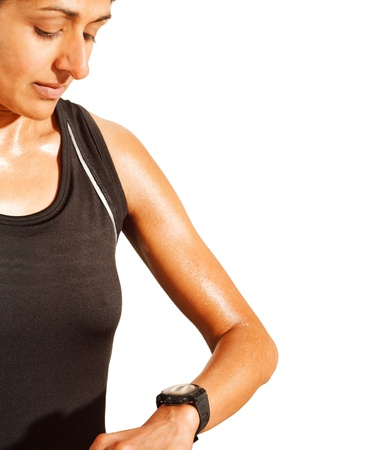 fitness goal: Indian woman athlete looks at her watch whilst training  Lots of white copyspace