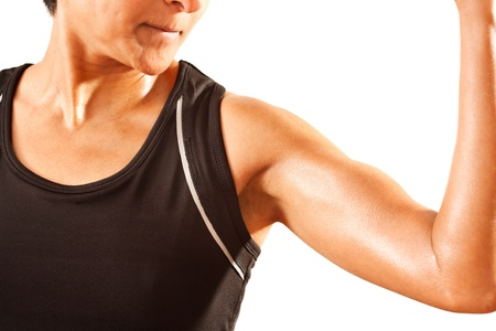 An athletic Asian Indian woman clenches her bicep  White background  photo