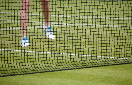 Female tennis player plays tennis on a grass court photo
