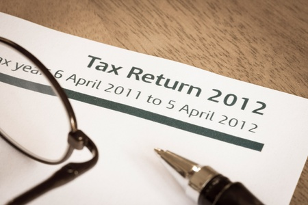 UK Income tax return form for 2012 on a desk with pen and spectacles Banco de Imagens