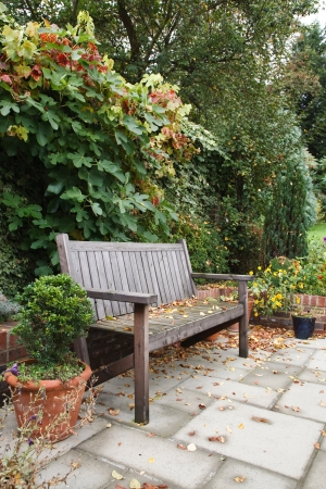 restful: Informal courtyard garden in autumn with a wooden bench and traditional paving patio Stock Photo