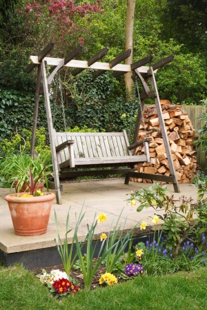 Relaxing suburban garden terrace with a swing bench