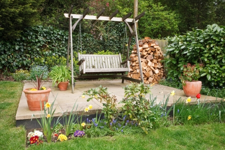 Relaxing garden patio with swing bench, potted plants and a wood pile