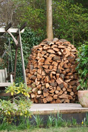 Circular wood stack or holz hausen with oak firewood seasoning in a garden photo