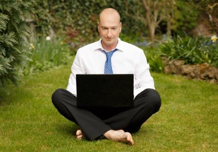 quiet adult: Imprenditore di successo in camicia bianca e cravatta a lavorare a gambe incrociate su un computer portatile in un giardino