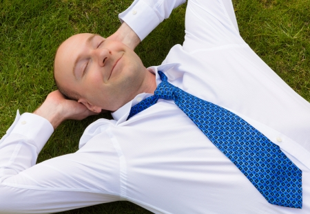 Businessman in shirt and tie relaxing on grass looking happy