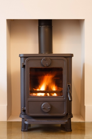 cast iron: Cast iron wood burning stove in a modern contemporary fireplace Stock Photo