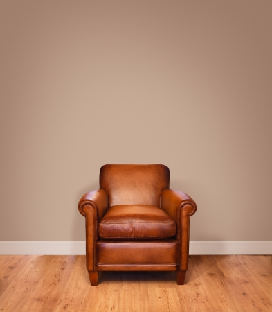 couch: Leather armchair on a wooden floor against a plain background wall with lots of copyspace  The wall has a clipping path  Stock Photo