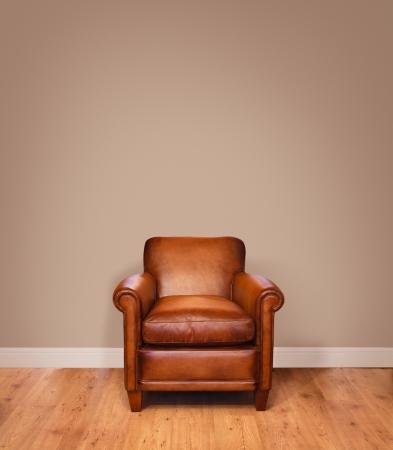 Lederen fauteuil op een houten vloer tegen een effen achtergrond muur met veel copyspace De muur heeft een clipping path