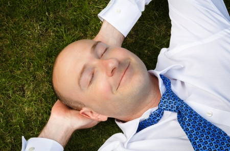 dozing: Closeup of an office worker resting lying on a grass lawn Stock Photo