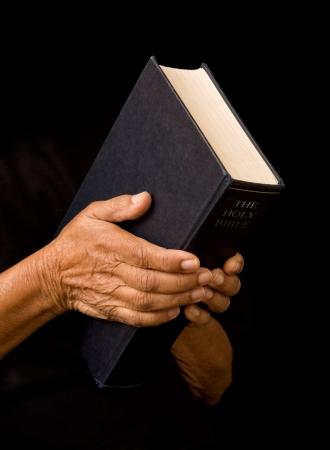 arrepentimiento: Una anciana sostiene una biblia en la oración