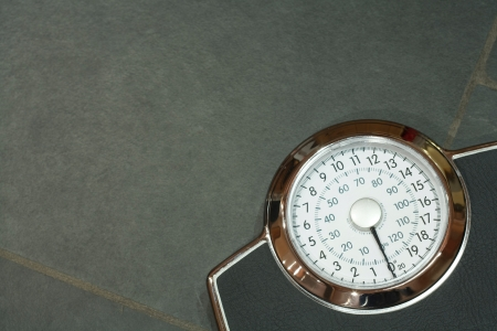 Bathroom scales on a slate floor with copyspace photo