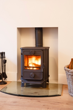 Cast iron wood burning stove in a modern contemporary fireplace Stock Photo