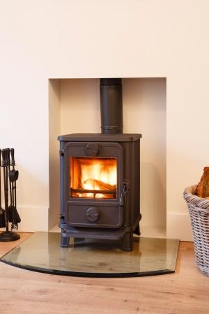 flue season: Reparto de madera estufa de hierro en una chimenea moderna y contempor�nea
