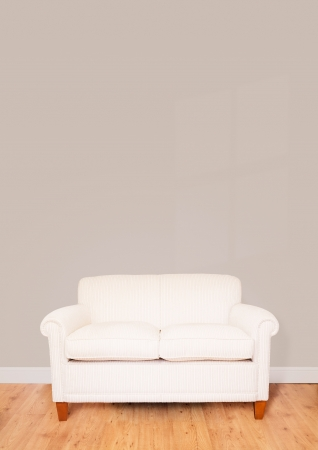 Modern cream sofa against a blank wall with lots of space for text photo