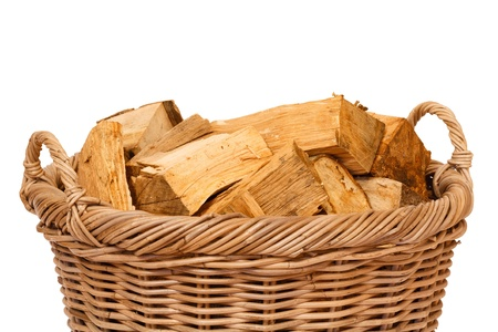 log basket: Closeup of a wicker log basket with oak logs isolated against a white background