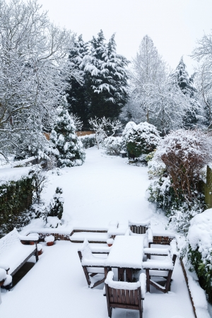 Suburban winter garden and patio furniture covered with snow