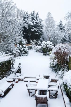 precipitation: Suburban winter garden and patio furniture covered with snow