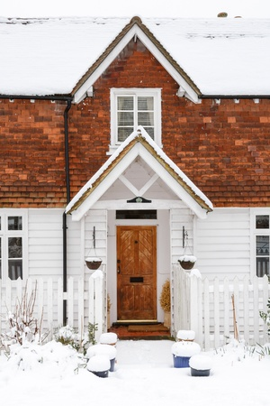 Front of clapboard home with snow on roof