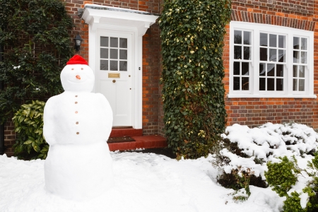 Snowman in front garden of home in winter photo