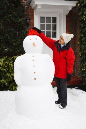 An Asian girl building a real snowman outdoors in a garden photo