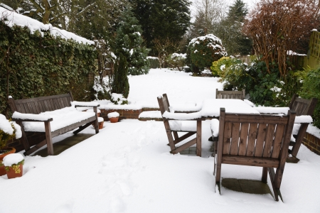 snowscene: Suburban snow covered patio with garden furniture, garden in the background