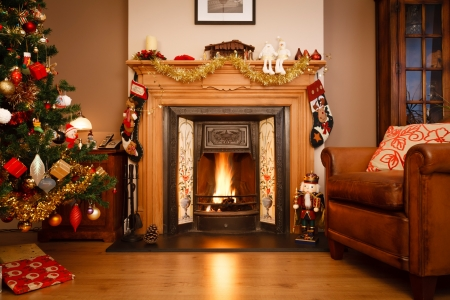 domestic scene: Decorated fireplace in a family home with Christmas tree