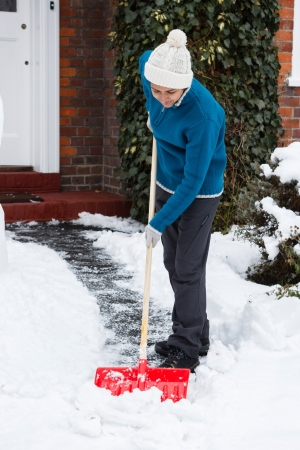 Person shovelling snow off driveway outside her house photo
