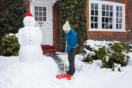 snow clearing: Woman shovels snow outside her home in UK Stock Photo