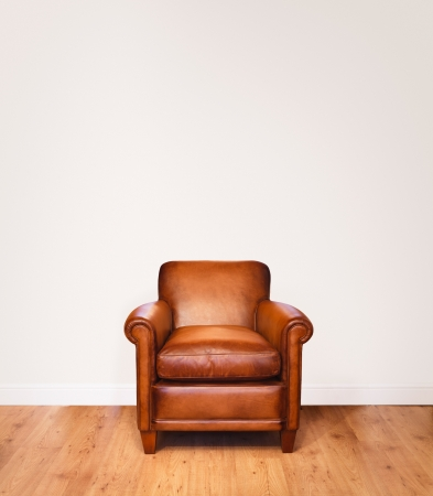 Leather armchair on a wooden floor against a white background with lots of space for copy.