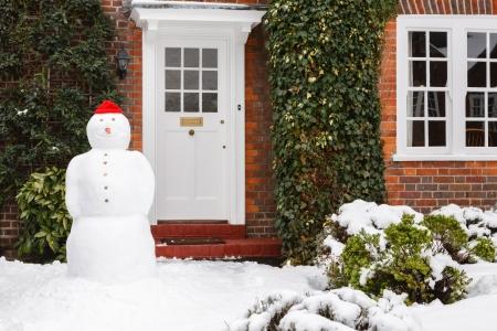 bonhomme de neige: Bonhomme de neige devant la maison en v�ritable sc�ne d'hiver