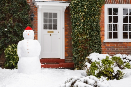 Real snowman outside house in winter scene photo