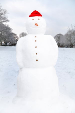 Winter landscape with snowman on a village green in England, UK photo