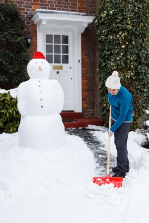 Adult shovels snow off path outside home Stock Photo