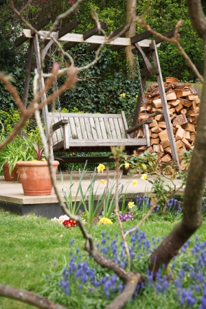 Relaxing summer garden back yard with flowers and a swing bench photo