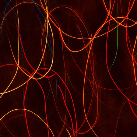 Red and orange light trails against a black background photo