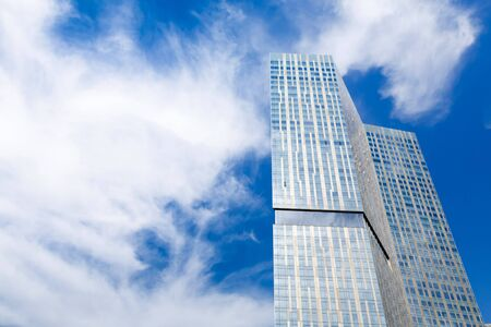 Modern glass skyscraper against a blue sky with copyspace