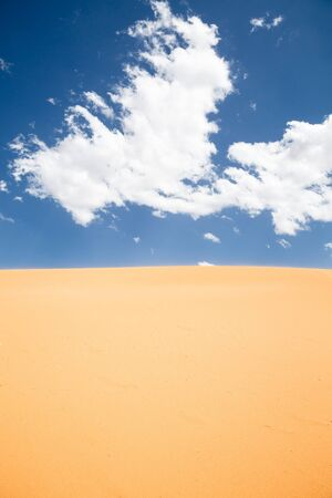 Barren desert landscape with colorful blue sky and clouds photo